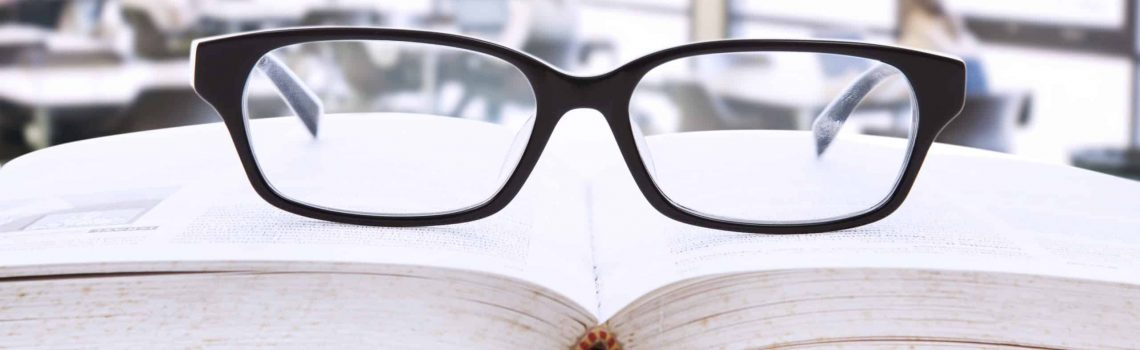 Picture of an open book with a glasses on top of it