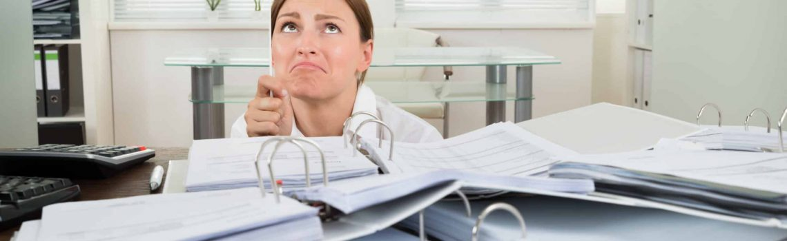 Unhappy Businesswoman Holding Flag With The Text Help In Front Of Invoices At Desk